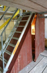 Blick auf Treppe und die Installation, ein Raum, welches direkt unter der treppe ausfüllt und von vorn (mit leicht geöffneter Türe) mit gebrauchtem Original-Holz. Innen ist eine Matratze sichtbar. Ein inneres Licht beleuchtet eine Tischplatte mit Büchern.