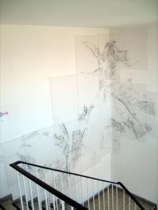 Treppenhaus-Wand, an der die große Arbeit hängt. Im Vordergrund sieht man einen Teil von der Treppe.