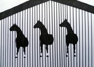 Drei Pferdeskulpturen ragen an der seitlichen Wand des Hauses heraus, schwarzweiß-Silhouette