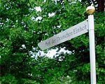 """Silbriges Straßenschild mit schwarzer Schrift """"Park der Deutschen Einheit"""" mit einer goldenen Kugel auf der Stange. Im Hintergrund ist das grüne Laub zweier Gingko-Bäume."""